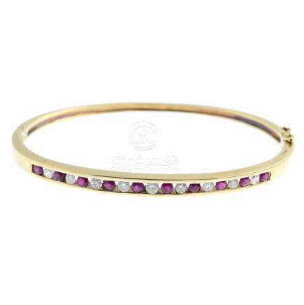 A 9ct gold diamond and ruby hinged bangle. Designed as an alternating brilliant-cut diamond and