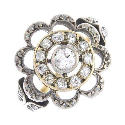An Edwardian silver and gold diamond cluster ring. Designed as an openwork flower, the old-cut