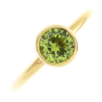 A peridot ring. The circular-shape peridot, within a collet setting, to the plain band. Ring size