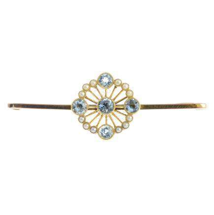 An early 20th century 9ct gold aquamarine and split pearl brooch. The circular-shape aquamarine,
