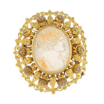 A shell cameo brooch. Of oval outline, carved to depict a woman in profile, within a foliate