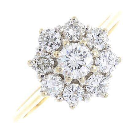 An 18ct gold diamond cluster ring. The brilliant-cut diamond, with similarly-cut diamond surround