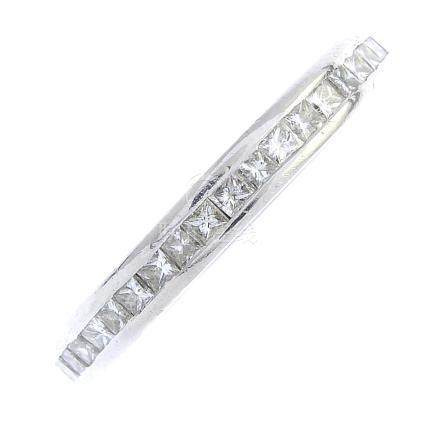 A platinum diamond full eternity ring. The square-shape diamond line, within a channel setting.