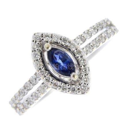 An 18ct gold diamond and sapphire cluster ring. The marquise-shape sapphire, with brilliant-cut