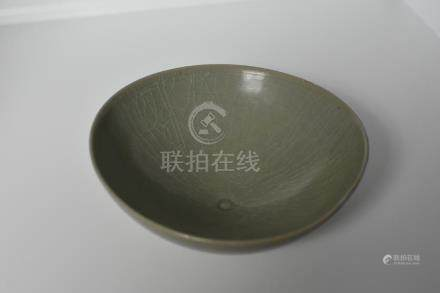 A celadon bowl with incised swimming fishes design