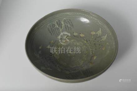 A celadon bowl with inlaid willow tree and waterfowl design