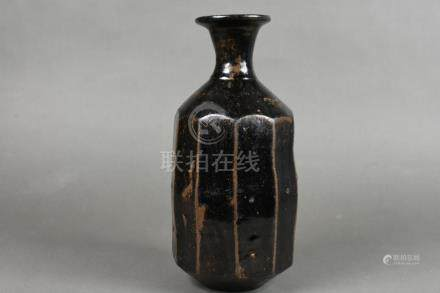 A black-glazed octagonal bottle