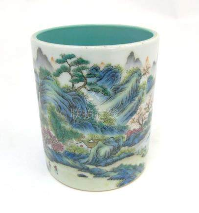 A Chinese famille rose brush pot painted in enamels depicting a continuous landscape scene of