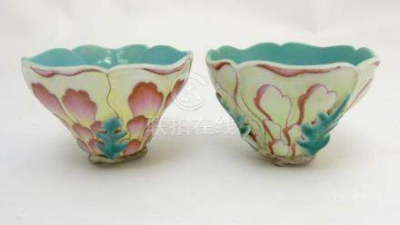 A pair of Chinese moulded flower cups formed as stylised peonies flowers balanced on leaves and