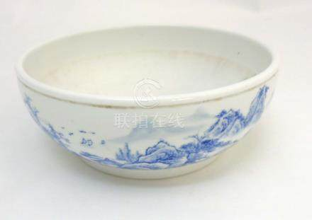 A Chinese blue and white bowl decorated in an underglaze blue continuous landscape and iron red