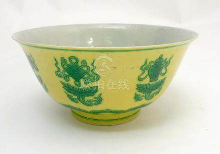 A Chinese bowl decorated with green auspicious items above a lotus flower head and scroll to yellow