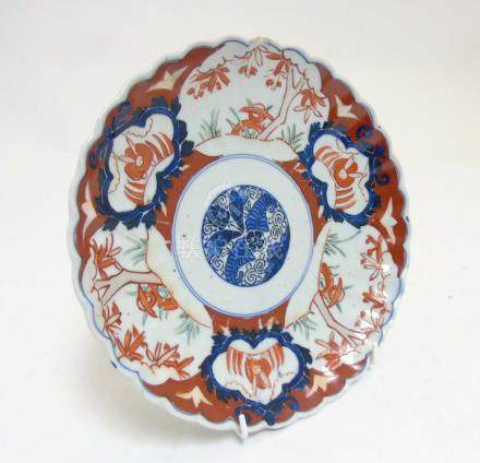 An Oriental Imari style plate with scalloped edges with stylized floral design to centre and other