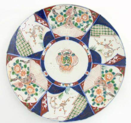 An Oriental charger having 6 panels of Japanese Imari decoration in iron red and blue around
