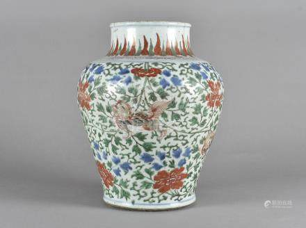 An Chinese porcelain Wucai vase, of baluster shape, decorated with Buddhistic lion dogs, against a