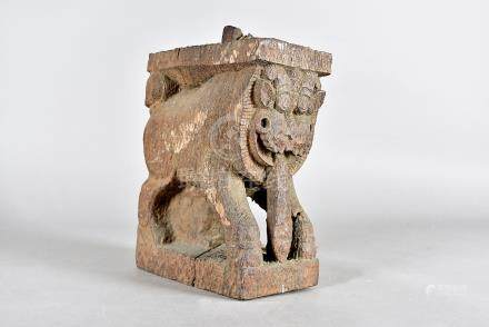 An early Indo Chinese carved temple dog, modelled with a protruding tongue in carved hardwood,