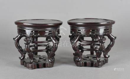 A pair of Chinese hardwood stands, with circular tops supported by five scrolls united by a pair