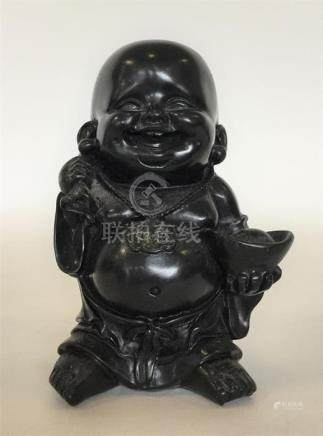 A carved wooden figure of Buddha carrying a loaded