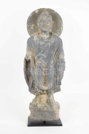 Bouddha auréolé debout sur une base à décor floralOn voit au-dessus de ses chevilles les pli