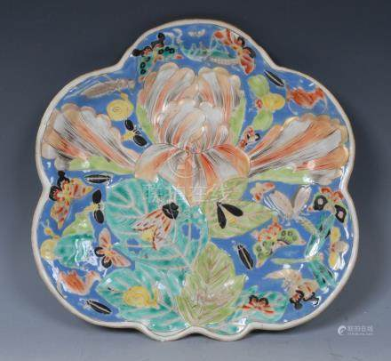 A Chinese shaped oval plate, decorated with large lotus flower, leaves and insects,