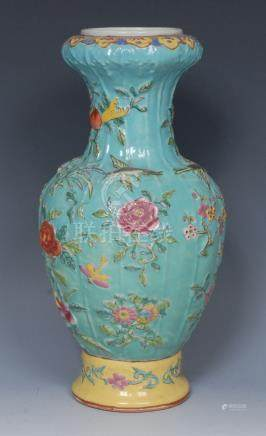 A Chinese baluster vase, ribbed in relief with blossoming prunus branches and foliage,