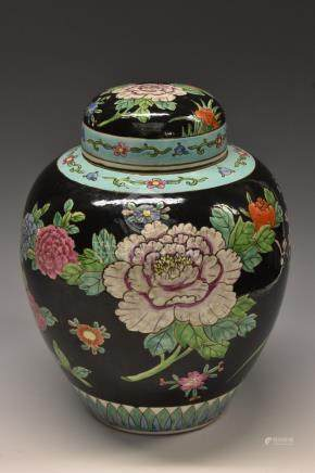 A Chinese famille noir ovoid ginger jar and cover, painted in polychrome with flowers,