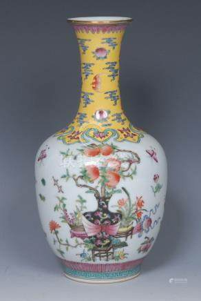 A Chinese Famille Rose bottle vase, decorated with peach bush, insects and precious objects,