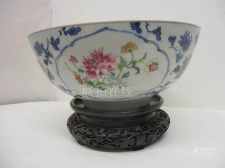 A late 18th century Chinese bowl decorated with panels of polychrome flowers, blue and white flowers