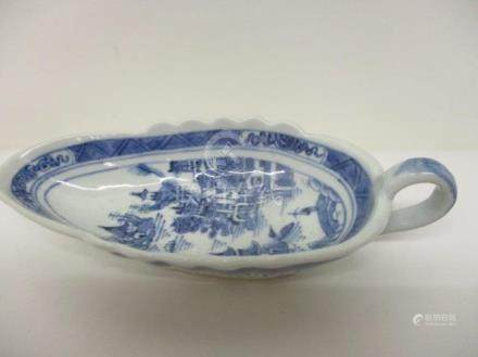 An early 19th century Chinese Canton blue and white sauce boat decorated with a river scene and