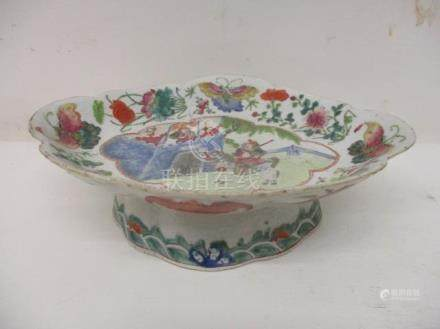 A late 19th century Chinese Canton dish of lobed form on a high foot, decorated with bats, fruit,