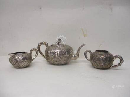 A late 19th/20th century Chinese silver three piece teaset by Wai Kee Hong Kong of bulbous form,