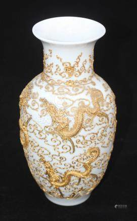 A Chinese porcelain vase of baluster form, profusely decorated with gilt tube-lined dragons, pagodas