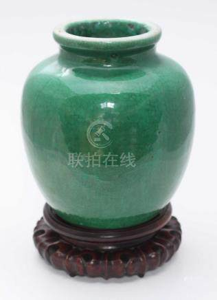 A Chinese Green Crackle-Glaze Vase, of ovoid form, on carved and pierced rosewood circular stand,
