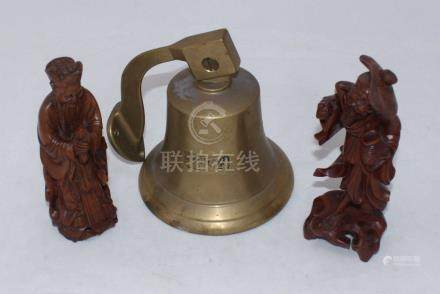 A brass ship's bell cast with the date 1834, together with two Chinese carved wooden figures