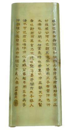 A Chinese green hardstone wrist rest modelled as a scroll with engraved verses of character marks