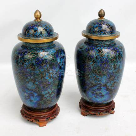 A pair of Chinese cloisonné enamel on blue ground lidded vases, both with wooden stands,