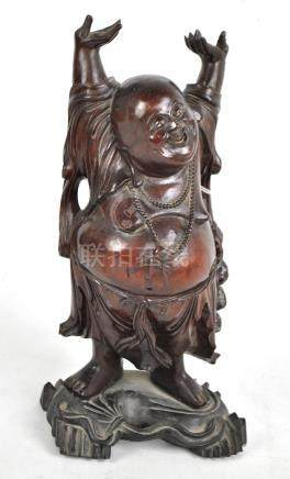 An early 20th century Chinese carved figure of a Buddha with arms raised aloft, height 40cm.