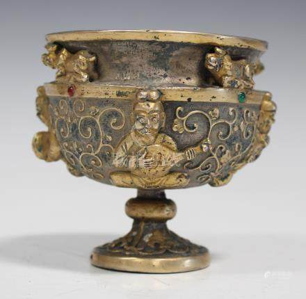 A Chinese gilt and silvered bronze cup, modern, cast in relief with a band of seated musicians