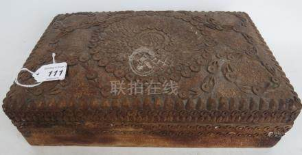 An Asian carved wooden box with floral decoration to all four sides and top,