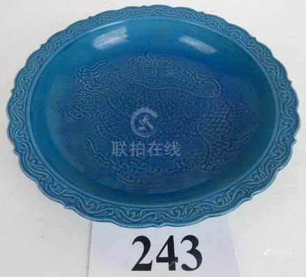 A Chinese period-style all over blue dish, relief decorated with a dragon amidst clouds,