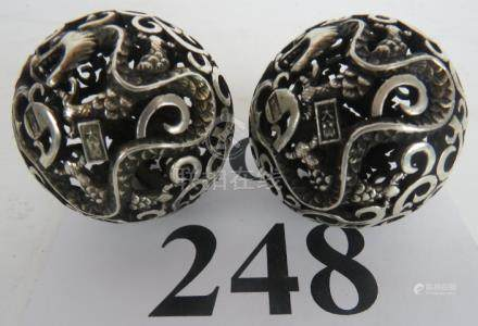Two Chinese white-metal spherical forms, decorated and pierced with character marks,