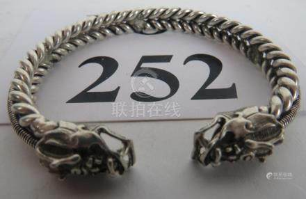 A delicate and decorative Chinese white-metal bracelet with dragons mask terminals,