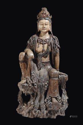 A large and important carved and polychrome wood figure of Guanyin seated on a rock, China, Yuan Dynasty (1279-1368)