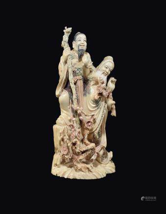 "A carved painted ivory ""two wise men with branches of roses"" group, China, early 20th century"