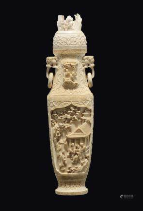 An ivory vase and cover with rings-handles carved with common life scenes within reserves, China, Canton, Qing Dynasty, 19th century