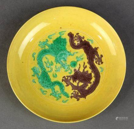 Chinese porcelain yellow ground dish, the well featuring a green and an aubergine dragon in