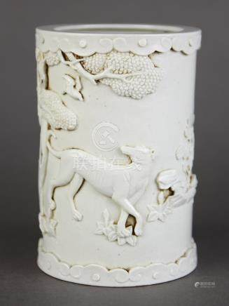 Chinese blanc de chine porcelain brush pot, featuring a hound below a tree, the rim accented with