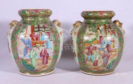 Pair of late 19th Century Chinese famille rose bulbous vases with faux mask and ring handles,