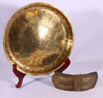 Islamic shallow bowl with punched scrolling flower decoration and a heavy brass buckle,