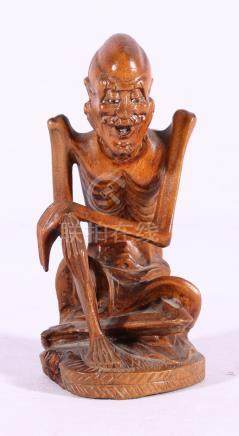 Chinese wooden carving of an emaciated lohan, with inset glass eyes, 13.5cm.