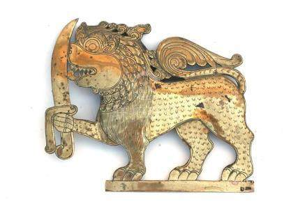 An Eastern brass plaque in the form of a stylised lion holding a sword, 14cms (5.5ins) high.